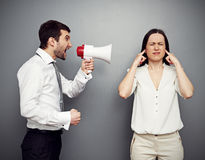 Man screaming in megaphone at the woman Stock Photo