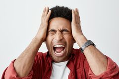 Man screaming from migraine. Close up portrait of black-sinned unhappy guy with afro hairstyle in white t shirt under. Red casual shirt squeezing head with Royalty Free Stock Photography