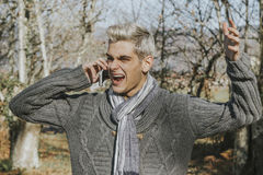 Man screaming with mobile phone. Young man screaming for outdoor mobile phone Stock Image