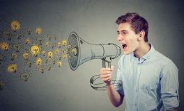 Man screaming out his ideas loud in megaphone. Isolated on gray wall background Stock Photography