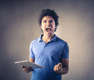 Man screaming out loud. A man who is holding a tablet, is screaming out loud Royalty Free Stock Photography