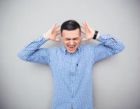 Man screaming over gray background Stock Photo
