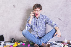Man screaming into phone. Crazy businessman sitting on messy desktop and screaming into phone Stock Photo