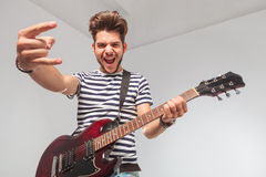 Man screaming while playing guitar and looking down Stock Photography