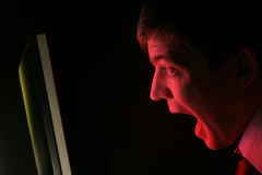 Man screaming at red monitor. A man in shirt and tie screams at a red computer monitor. Anger? Frustration? Fear Royalty Free Stock Photo
