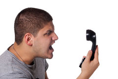 Man Screaming Into the Telephone. An angry and irritated young man yells into the telephone receiver over a white background Royalty Free Stock Photo