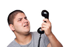 Man Screaming Into the Telephone. An angry and irritated young man yells into the telephone receiver over a white background Royalty Free Stock Photos