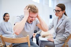 Man screaming. Troubled or stressed young men screaming while psychologist trying to support him during session Stock Images