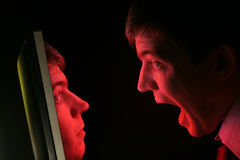 Man screams at face in monitor. A man in shirt and tie screams at a red computer monitor as his own face emerges from it Royalty Free Stock Photos
