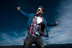 Man screams with hands in the air and celebrates success. Young happy casual man screams with hands in the air and celebrates success with mountains and blue sky royalty free stock image