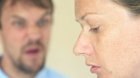 The man screams at the woman. The face of a woman in profile is close-up, the face of a man is blurred.