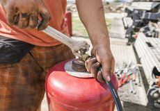 The man the pipe to the gas cylinder with a wrench. royalty free stock image