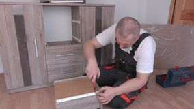 Man with screwdriver mounted drawer. In room stock video footage