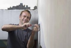 Man Screwing Bracket into Wall - Horizontal royalty free stock photography