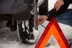 Man screwing a car wheel on a snow road. Ð•mergency sign stock photos