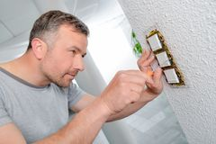 Man screwing row three switches to wall Stock Image