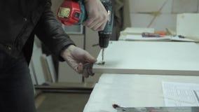 Man screws hinge into cabinet stock video footage