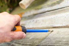 Man screws a in a wooden structure royalty free stock images
