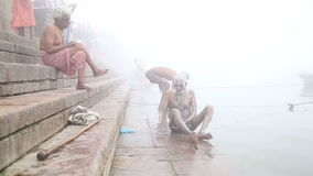 Man scrubbing his body on shore of foggy Ganges river in Varanasi. VARANASI, INDIA - 19 FEBRUARY 2015: Man scrubbing his body on shore of foggy Ganges river in stock video footage