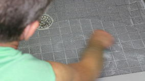 Man Scrubbing a Shower Floor. Male leaning into a shower, scrubbing a tile floor with a scrub brush and soap. Gray tile floor with grout being cleaned by an stock footage