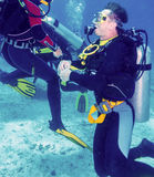 Man Scuba Diver Kneeing at Sand Bottom Stock Image