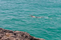 Man in a scuba mask swims in blue sea water. Image of man in a scuba mask swims in blue sea water Royalty Free Stock Photo
