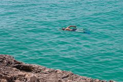 Man in a scuba mask swims in blue sea water. Image of man in a scuba mask swims in blue sea water Stock Images