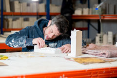 Man Sculpting Plaster Model Buildings. A man in paint-splattered dark hoodie busy scuplting a white plaster building model using a precision knife on a drafting Royalty Free Stock Photos