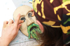 Man sculpting plasticine face with moustache Stock Photography