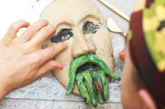 Man sculpting plasticine form of face Royalty Free Stock Image