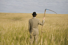 Man with scythe. Man in suit and hat with scythe standing in field with golden grass Stock Photos