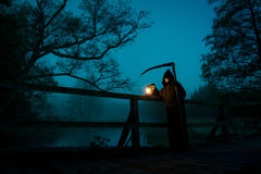 Man with scythe and oil lamp looks like death. In the night Royalty Free Stock Images