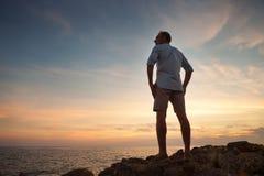 Man on the sea coast look on the sunset Stock Photo