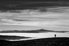 Man and sea of fog. A man in a mountains scenery, with fog filling a valley and a big, deep sky Stock Photos