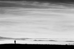 Man and sea of fog. A man in a mountains scenery, looking at a valley filled by fog and beneath a big, deep sky Royalty Free Stock Photography