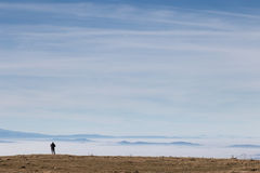Man and sea of fog. A small human figure on top of a mountain, beneath a huge sky, looking at a sea of fog Royalty Free Stock Image