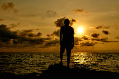 Man and the sea. Silhouette of a man standing on a rock by the sea at sunset stock photography