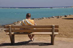 Man and the sea. Man sits on the bench and looking the blue waters of the Red sea and dreams Royalty Free Stock Image