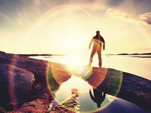 Man at sea. The sky and the man are reflected in a smooth water. In front of the sea Stock Image