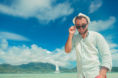 Man by the sea smiling and fixing his sunglasses Royalty Free Stock Photography