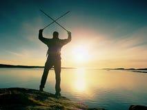 Man, sea and sun at horizon. Traveler on rocky cliff above sea enjoy view. Royalty Free Stock Photos