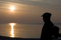 Man by sea at sunset. Silhouetted man with cycle helmet by sea at sunset Stock Photography
