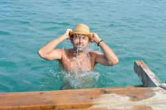 Man in sea wearing a hat full with water Stock Photos