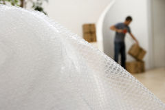 Man sealing box with tape at home, focus on bubble wrap in foreground Stock Photo