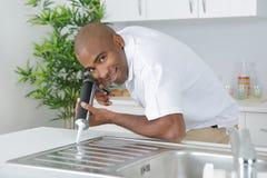 Man sealing edge kitchen sink. Man sealing edge of kitchen sink royalty free stock photos