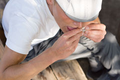 Man sealing the paper of a rolled cigarette. High angle close-up of a man wearing a white cap sealing the paper of a rolled cigarette Royalty Free Stock Image