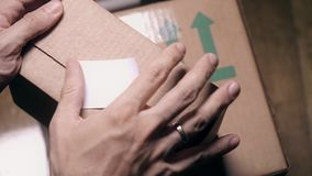 Man sealing parcel carton box with a white sticker. Man sealing parcel carton box with a sticker stock footage