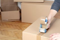 Man sealing a shipping cardboard box. With tape dispenser. Indoors stock photo