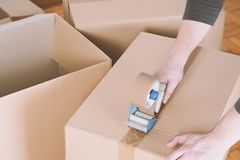 Man sealing a shipping cardboard box. With tape dispenser. Indoors stock image