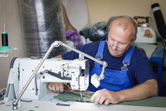 Man seamsrtess sitting at the sewing machine stock image